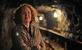 Julia Wolfe stands with her arms crossed in an underground mineshaft.