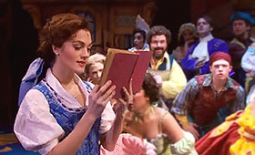 Belle quietly reads a book while townspeople sing around her.