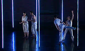 Dancers gesture while standing in front of floor-to-ceiling neon lighting.