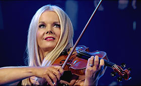 A close up photo of a young blond woman playing the fiddle.