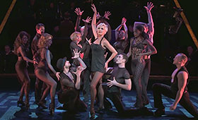 Roxie stands on stage with her arm in the air while surrounded by dancers.