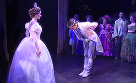 The prince bows to Cinderella before they begin to dance as a crowd watches on.