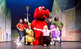 Seven actors and two small dog puppets stand around a big red dog puppet in the middle of a stage set.