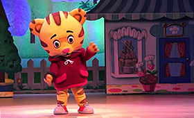 An actor dressed in an oversized Daniel Tiger costume makes a gesture with his left paw.