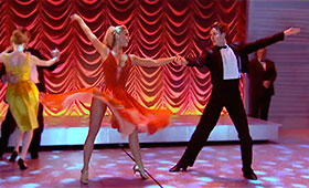 A woman in a twirly skirt and a man in a tuxedo dance together with their arms extended.