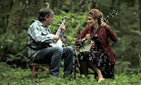 Fleck and Washburn play their banjos in a lush forest.