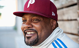 Harris smiles on the street wearing a track jacket and Phillies baseball cap.