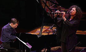 Fred Hersch looks down at the keys while he plays the piano as Anat Cohen points her clarinet straightforward while playing it.