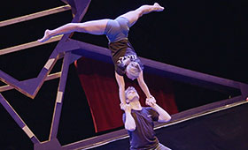A male acrobat holds another's hands while she straightens her body into an upside-down split position.