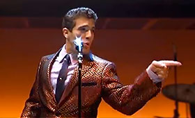 A man, wearing a shiny suit, sings in front of a microphone while pointing off stage.