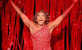 An actor wearing a shiny sequin dress stands in front of a stage curtain with arms outstretched.