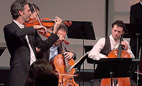 Two violinists and two cellists perform on stage.