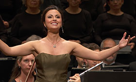 A woman stands in front of sitting musicians and outstretches her arms as she smiles at the audience.