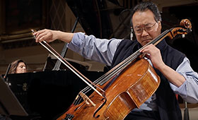Yo-Yo Ma plays the cello while Kathryn Stott plays the piano behind him.