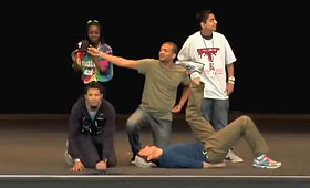Two men crouch on the ground next to a third on his back while two students stand behind them on stage.