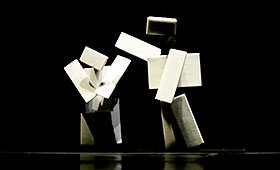 Two humanoid figures composed of boxes stand on stage. One taps the shoulder of the other.