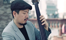 A double bassist wearing a beret-style cap looks down at his instrument as he plays.
