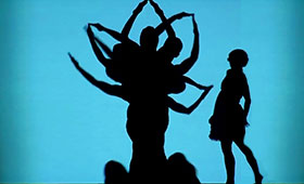 Dancers pose behind a screen to create a silhouette of a flowering plant while the silhouette of a young girl approaches it.