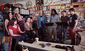 The members of Roomful of Teeth gather around three music stands and in front of various bookcases in a photo taken during an NPR Tiny Desk Concert.