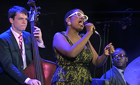 Salvant sings into the microphone as a bassist and drummer perform beside her.