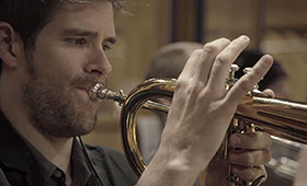 A trumpet player is shown performing close up.