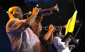 A row of men trumpeters perform on stage.