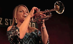 Jazz musician Bria Skonberg holds her trumpet up to her mouth during a performance at New York City club Jazz Standard.