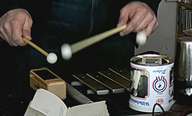 A close-up on a pair of hands playing the xylophone.