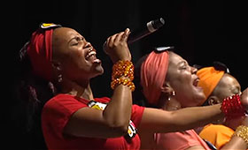 A woman wearing a headscarf and many bracelets closes her eyes while she sings into a micrphone.