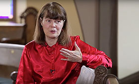 Alison Mackay sits while she gestures with her left hand and discusses her program J. S. Bach: The Circle of Creation for Tafelmusik Baroque Orchestra.