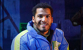 Christian Thompson wears a puffy winter coat on the stage of RENT.