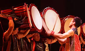 A man plays a row of large drums, each supported on the shoulders of other musicians.