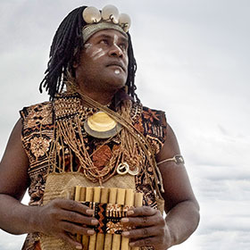 A musician wearing indigenous clothing holds a wind instrument while looking out at the ocean.