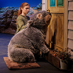 A human-sized wombat puppet sits in front of a door.