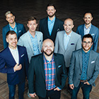 Eight male singers wearing sport jackets and button-up shirts stand in a huddle and smile at the photographer.