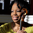 A woman holding a violin smiles and looks at something off-camera to her right.