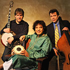A banjo player and a double bassist stand and hold their instruments while a man sits between them and smiles.
