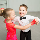 A young boy and girl dance in a ballroom.