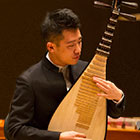 A man plays a traditional Chinese stringed instrument.