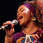 A woman wearing a headband and adorned with jewelry closes her eyes and sings into a microphone.