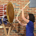 A women beats the front of a large Taiko drum.