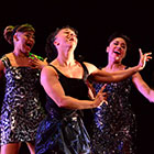 Three women in shiny dresses passionately sing with the arms in the air.